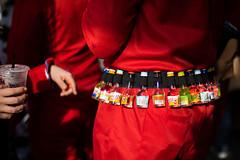 Man at carnival carrying little bottles with hard liquor on a waist belt