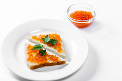 Two triangular sandwiches with salted red caviar on white background