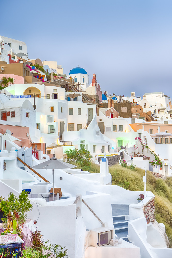 Cityscape of Oia Village on Santorini Island with Caldera Mountains On Background in Rays of Setting Sun.