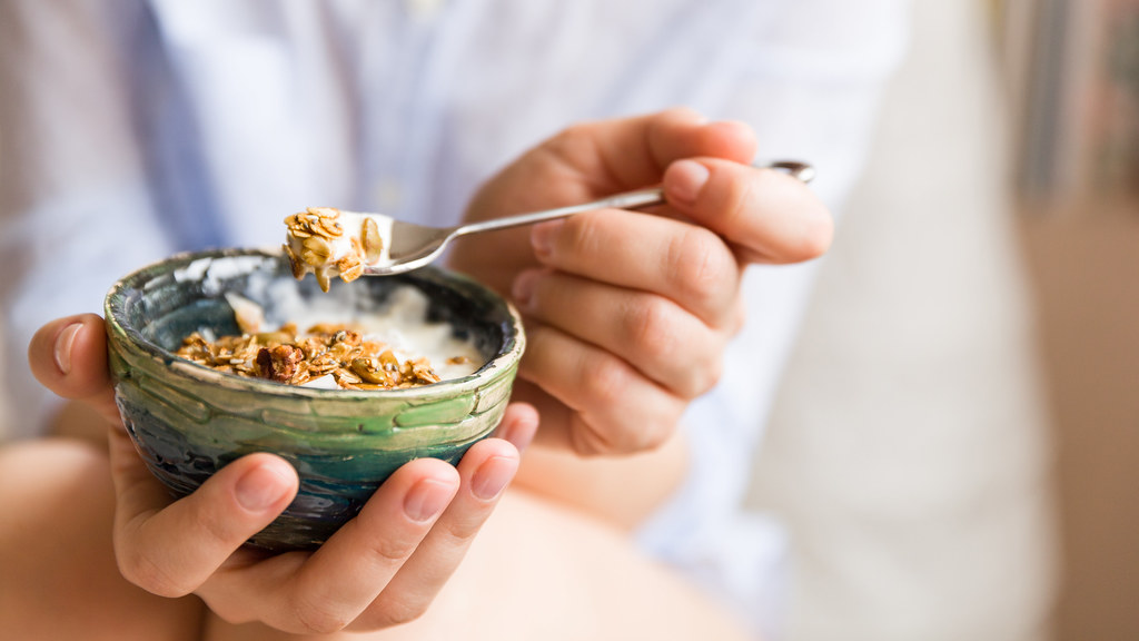 Girl eating breakfast cereals with nuts, pumpkin seeds, oats and yogurt in bowl