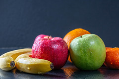 Bananas, apples and citrus with water droplets on black background
