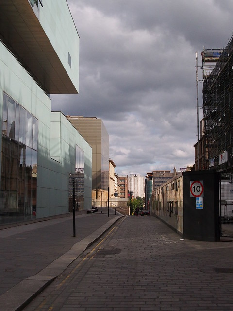 Looking downhill down a street narrowed by fenced-off building works on the right hand side. The modern building facade on the left shows the reflection of a much older building on the opposite side which is not directly visible behind the fencing.