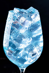 Close-up of blue cocktail with ice cubes in the glass