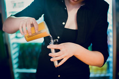 Lady bartender filling up a guest's flask with hard liquor