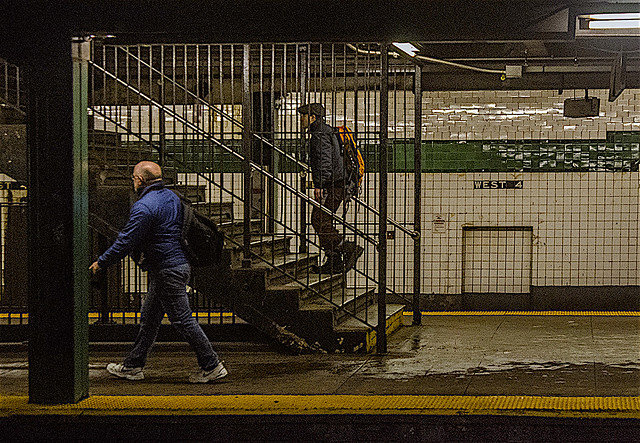 Candid of People at West 4th Subway Station Platform Manhattan on a wet cold day in January