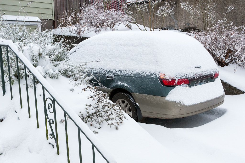 Our 2000 Subaru Outback sits in the driveway buried under snow in the Irvington neighborhood of Portland, Oregon