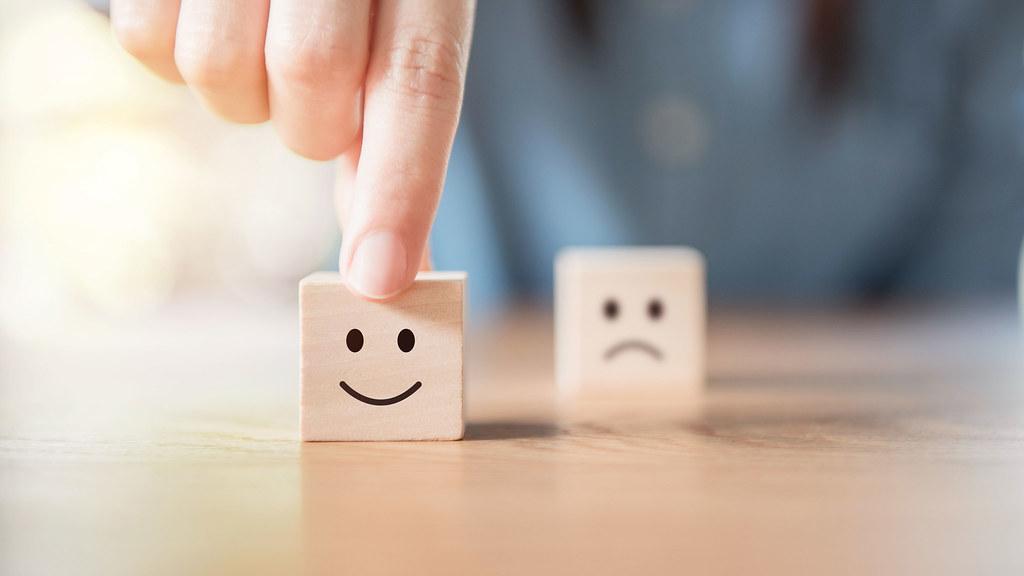 两个小方块,前景是一张笑脸,背景是一张悲伤的脸.