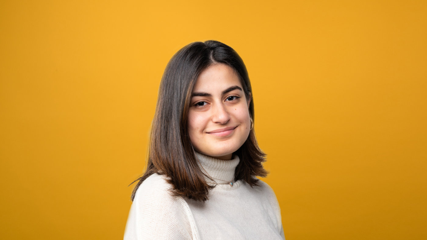 Dilara smiles at the camera against a yellow backdrop