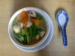 Fresh asian vegetable Soup in white bowl with a blue porcelain rice spoon on a wooden table