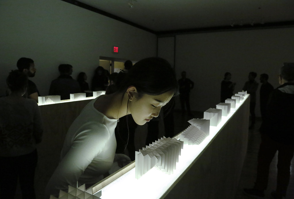 Ihwa Choi (B.Arch. '20) studies a model during the reception for the Labics exhibition <em>Structures</em>, in John Hartell Gallery.