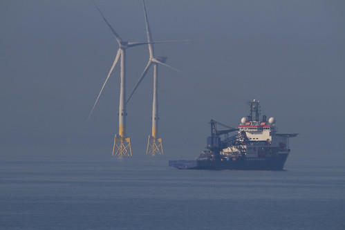 at 600mm: on a sleep, hazy, summer afternoon an oil supply vessel passes in front of majestic wind turbines, viewed from Torry Point, Girdle Ness, Aberdeen, Scotland