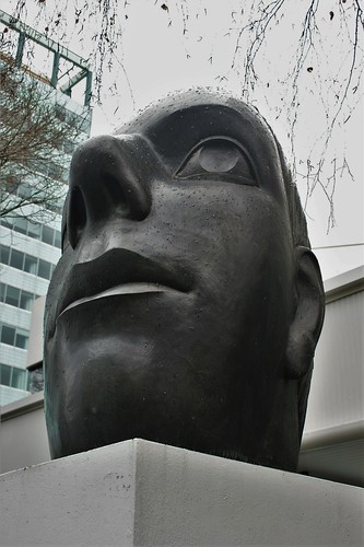 "<p>Created by Terry Stringer in 1987, this enormous bronze head was commissioned for $40,000 by Renouf Properties Ltd. <br /> It looks as though it is the last remaining piece of a huge ancient statue of a Roman emperor. Intentionally distorted perspective makes ""Grand Head"" look naturalistic from only some angles.<br /> ==========<br /> Sir Francis Henry ""Frank"" Renouf (31 July 1918 – 13 September 1998) was a NZ businessman and financier.<br /> He was a stockbroker from 1950 as a partner in the Wellington stockbroking firm of Daysh, Renouf & Co (the firm was originally Daysh, Longuet and Frethey). He introduced unit trusts to NZ, and founded the country's first merchant bank, the New Zealand United Corporation. <br /> He initiated the first NZ share index in 1957; the NZUC index and the first listed property company, Property Securities Ltd. He was the first to provide underwriting services for equity and local authority debt issues. <br /> Renouf set up three companies in 1981; Frank Renouf & Co, Renouf Corporation Ltd and Renouf Properties Ltd. The latter went into liquidation in 1991...but the head sculpture remains on the street outside the company's registered office at 88 Victoria St., Wellington. <br /> Renouf was knighted in the 1987 New Year Honours List, for philanthropic services.</p>"