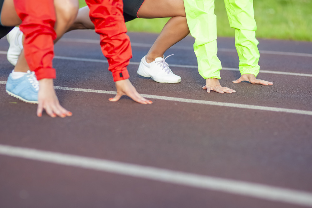 Closeup of Hands Of Two caucasian Athletes Standing Prepared For Running on Track Course.