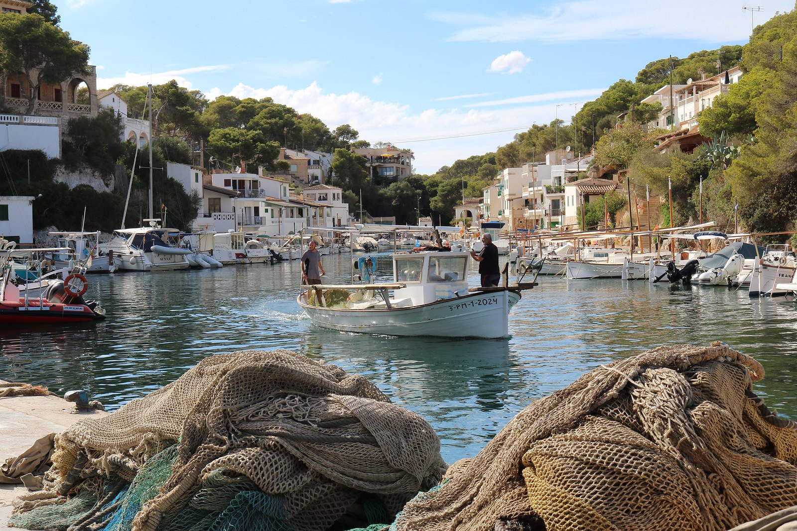 A fishermen's port in Cala Figuera, sorunded by small white houses and with a fishing boat sailinf off, in the centre of the picture. Mallorca Island, Spain