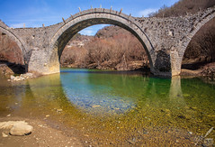 "The Plakida or Kalogeriko arched stone bridge, over the Voïdomátēs river, near Kēpoe (Κῆποι), Greece.  This 3-arch bridge's construction was funded in 1814 by a local monk (in Greek kalógero) with the sum of 20,000 kuruş (or piastres, in Greek γρόσσια). It was repaired in 1865.  The bridge is 65 m (213 ft) long.  Kēpoe is one of the 46 Zagori villages or Zagorochória. They are all built in high altitude, on Pindus range of mountains, in northwestern Greece. Zagori is an area of great natural beauty, with striking geology and two National Parks (one including the Aōos river and the Vikos Gorge, the other around Valia Kalda, to the east of the imposing snow-capped Mt Tymphē).  The reflection beneath the shot bridge reminds the poem lines:  ""And at the end of all How are we better off than Seaghan the fool, That never did a hand's turn? Aibric! Aibric! We have fallen in the dreams the Ever-living Breathe on the burnished mirror of the world And then smooth out with ivory hands and sigh, And find their laughter sweeter to the taste For that brief sighing.""  —William Butler Yeats (The Shadowy Waters)"