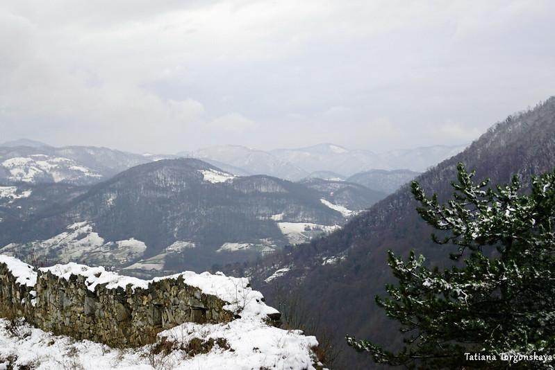 Фрагмент крепостной стены и заснеженные горы
