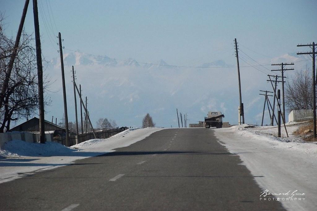 Route en hiver à l'entrée de la vallée de la Tounka. En arrière plan, la chaîne des Saïans orientaux © Bernard Grua