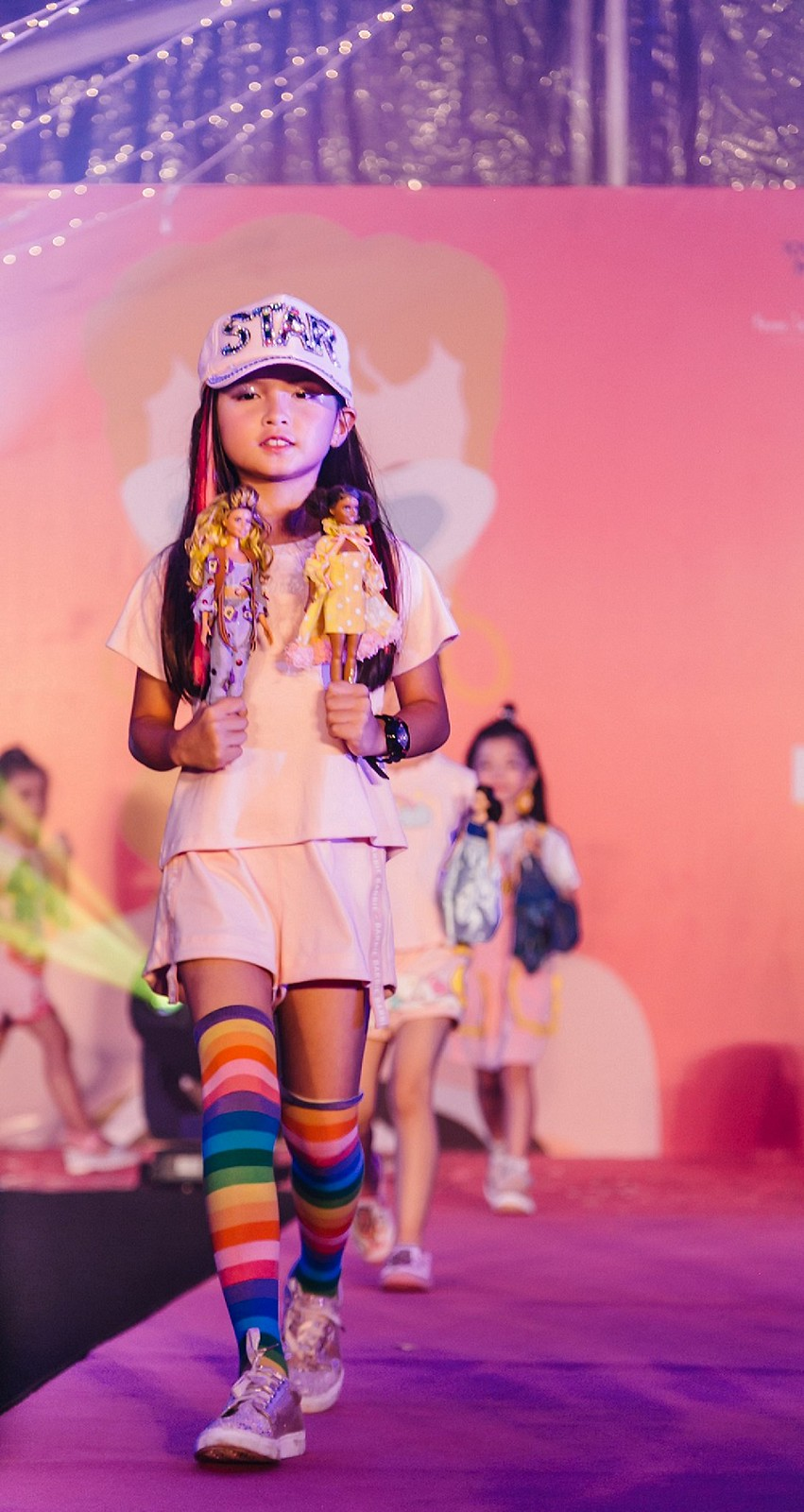 A Junior Supermodel from the Amber Chia Academy showcasing the Custom Styled Barbie Dolls by students of Limkokwing University and the A Cut Above Academy.