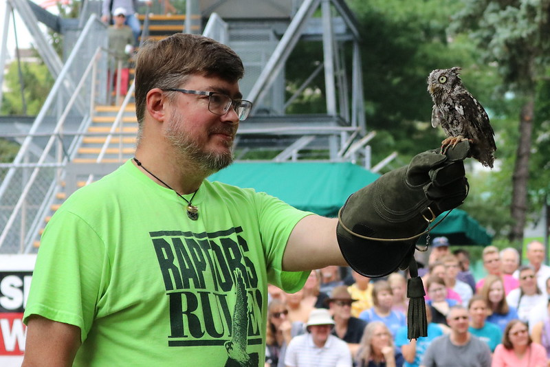 A man wearing a green Raptors Rule t-shirt while holding a small owl on his finger.