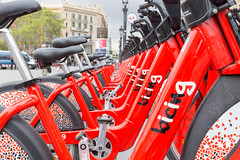 """Close-up of red bikes in a row to rent from """"bicing"""" in Barcelona, Spain at Plaça de Catalunya"""