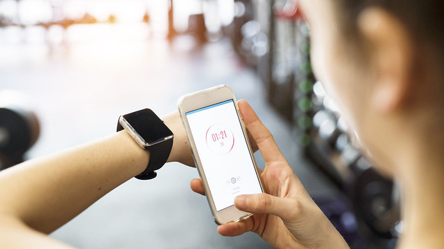 Woman using a fitness app on her smart phone and smart watch for tracking progress of her work out.