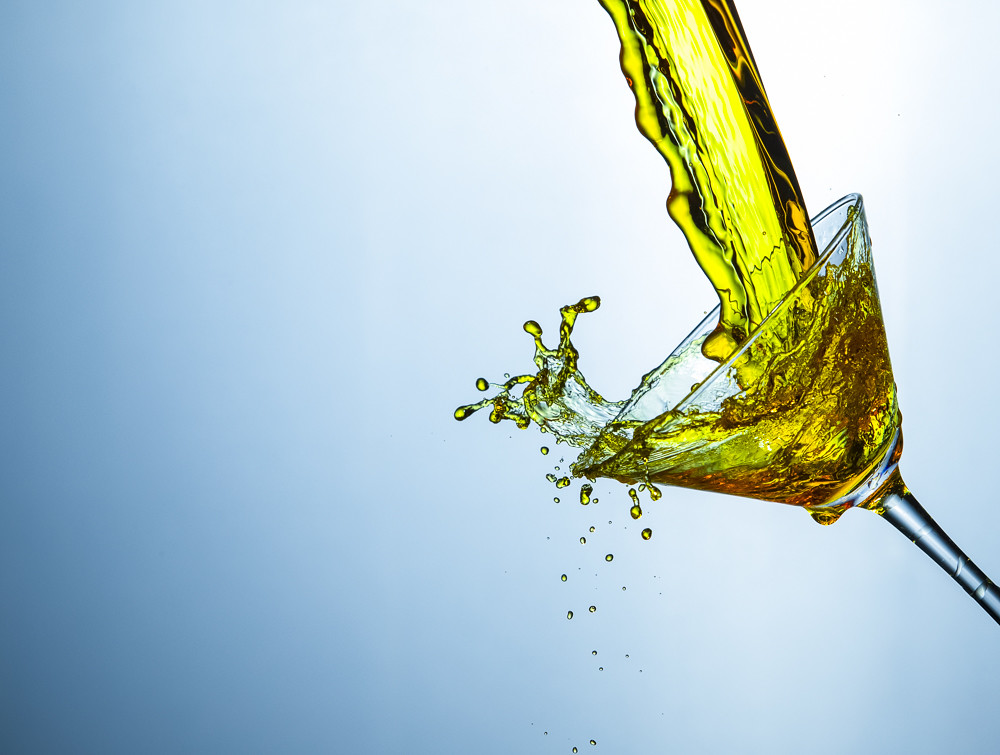 High Speed Liquids Photography. Colofur Drink Stream Poured Out of The Clear Wine Glass.