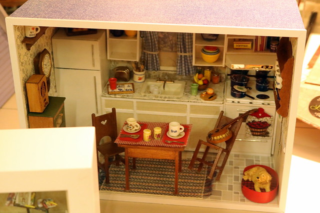 Diorama of a kitchen with a fridge, stove with pots, wallpaper, tile floor, granite countertops, and more.