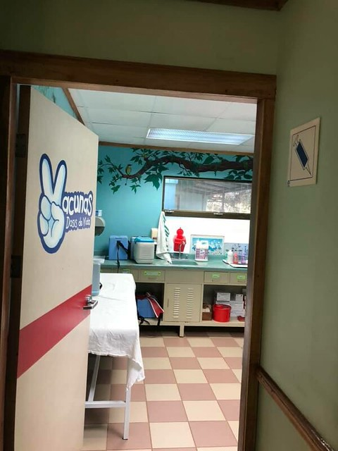 An open door to a room with a tree painted on the wall. Hospital supplies are on the counters next to a table covered with linen.