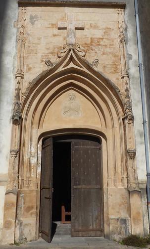 Saint André de Seignanx, Landes:  portail en pierre du XVe siècle de style flamboyant, surmonté d'un arc en accolade et orné, sur son tympan, d'une effigie en bas relief.