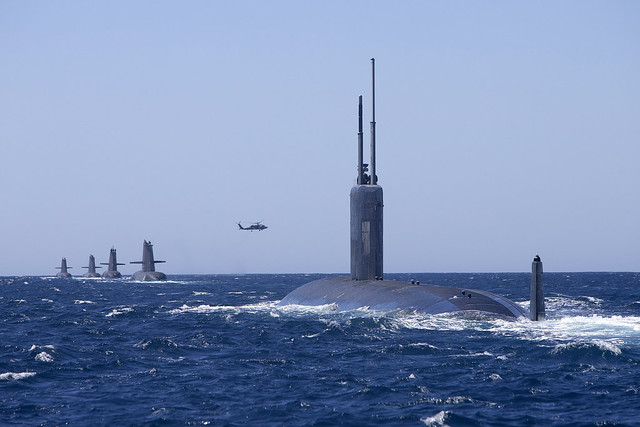 INDIAN OCEAN (Feb. 18, 2019) The Los Angeles-class attack submarine USS Santa Fe (SSN 763) sails in formation with Royal Australian Navy Collins class submarines HMAS Collins, HMAS Farncomb, HMAS Dechaineux and HMAS Sheean, as an Australian MH-60R Seahawk helicopter flies overhead in the West Australian exercise area. The submarines are participating in a number of activities, including Exercise Lungfish 2019 and Exercise Ocean Explorer 2019. (Royal Australian Navy photo by LSIS Richard Cordell)