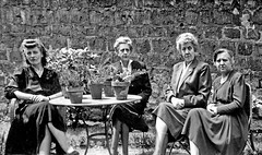 Vintage B&W. July 1953. France. Portrait of four ladies sitting in the sun in a garden.