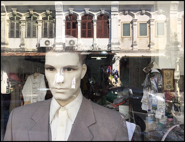 Reflected old street in tailors window