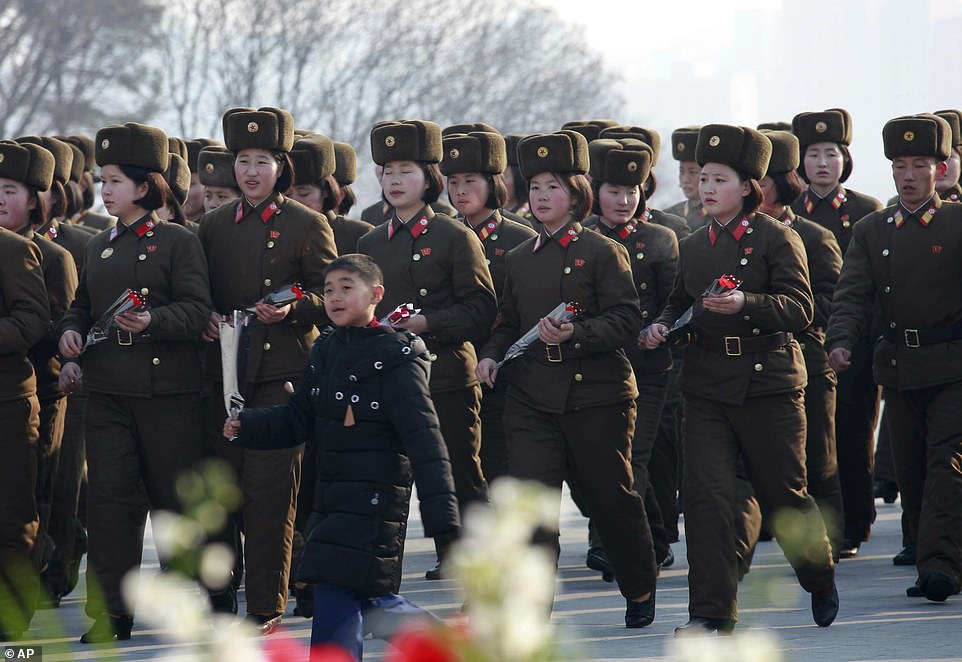 Soldiers carry flowers to lay below the statues of former North Korean leaders Kim Il-sung and Kim Jong-il on Mansu Hill in Pyongyang, Saturday, February 16, 2019. Associated Press photo.