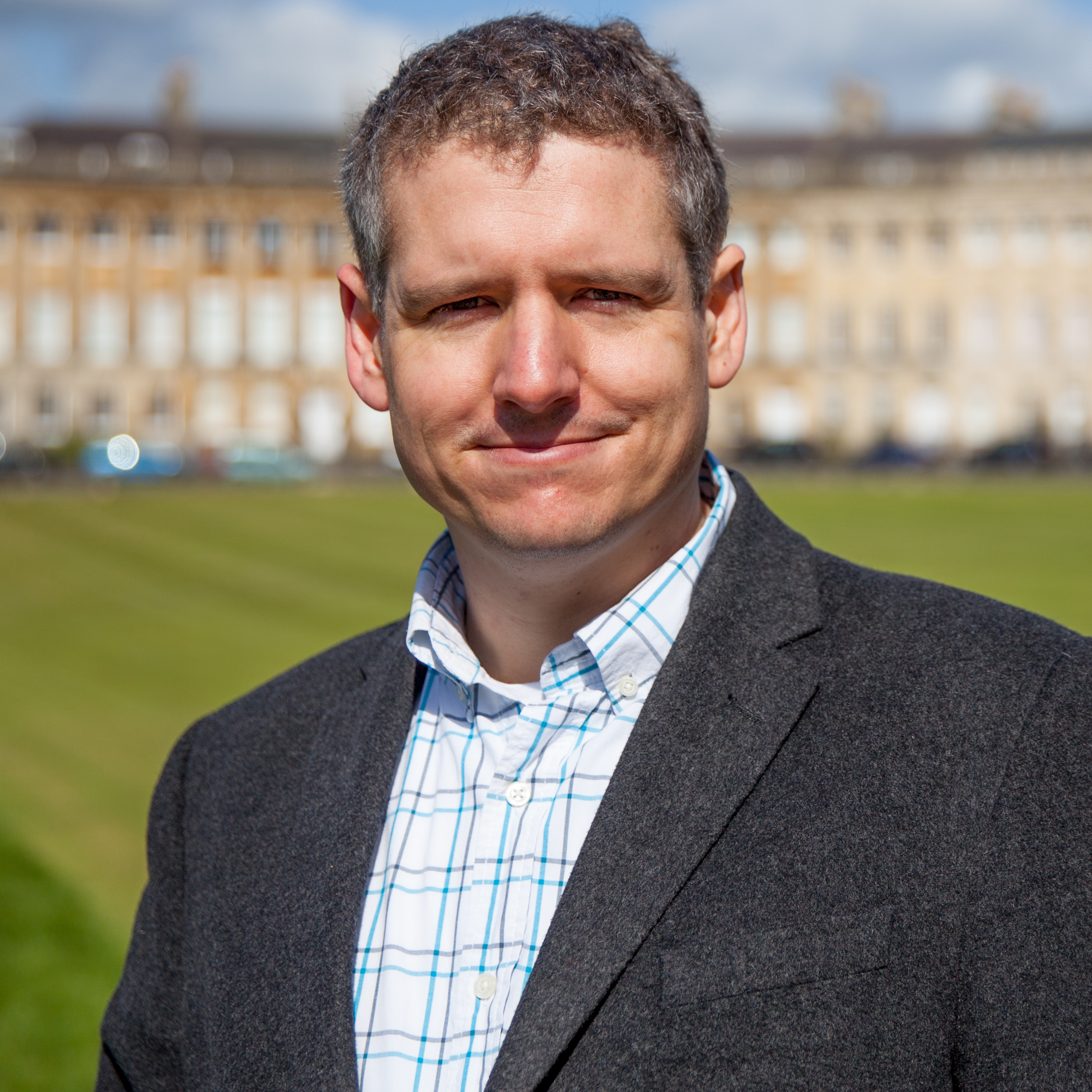 Photograph of Dr Robin Shields standing in front of the Royal Crescent on a sunny day
