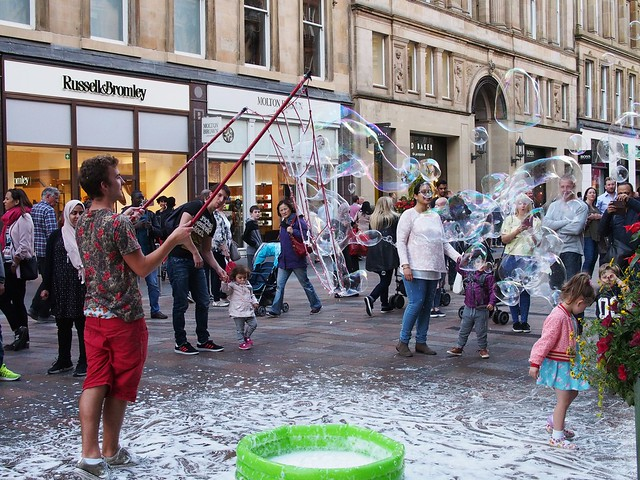 man in red shorts and floral shirt holding a large net on two poles and making large soap bubbles. There is a lot of white soap on the ground and several adults and children watching.