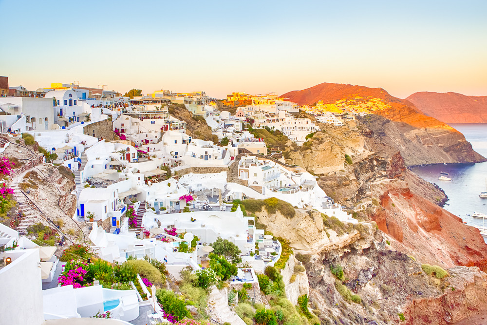 Romantic Destination. Picturesque Cityscape of Oia Village on Santorini Island with Caldera Mountains On Background in Rays of Setting Sun
