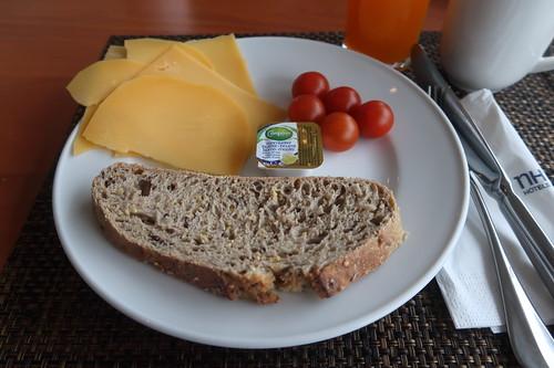 Käsescheiben zu braunem Brot mit Butter und kleinen Tomaten