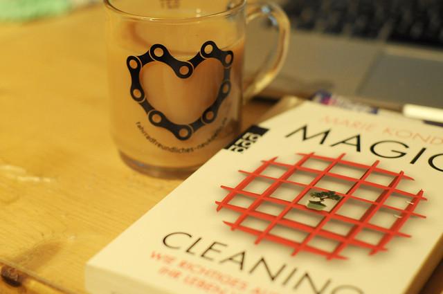 Ein Glas Tee mit einem Herz aus Fahrradkette und daneben Das Buch Magic Cleaning von Marie Kondo.