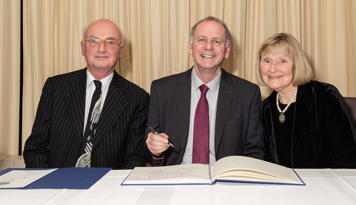 Godfrey and Sue Hall sign the Vice-Chancellor's Roll of Honour with Professor Bernie Morley