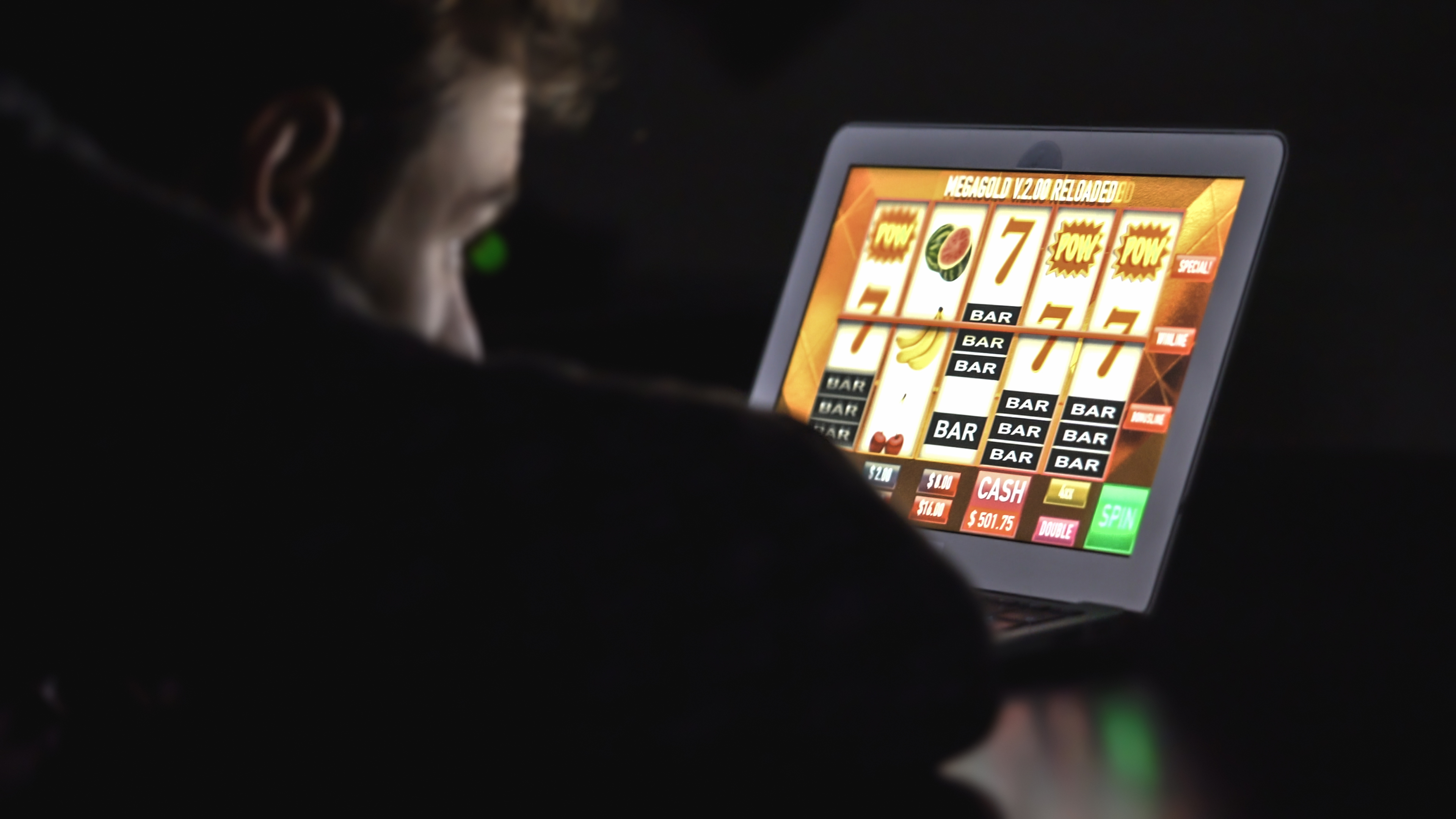 Gambling addicted man in front of online casino slot machine on laptop computer at night.