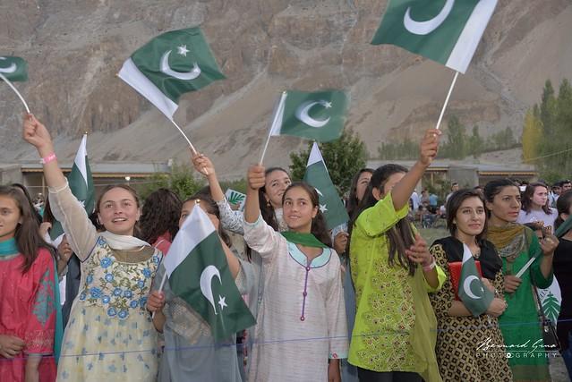 Jeunes femmes de la haute vall饠de la Hunza agitant des drapeaux pakistanais lors du festival FACE