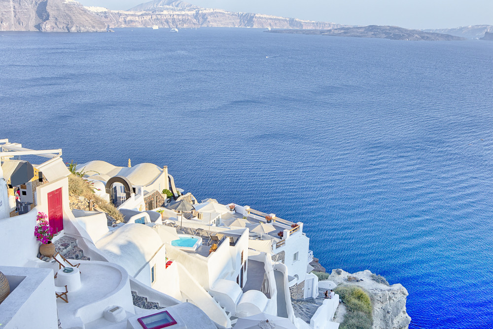 Famous Destinations. Breathtaking View of Classic White Roofed Houses and Pastel-Blue Colors of Oia Village on Santorini Island in Greece.