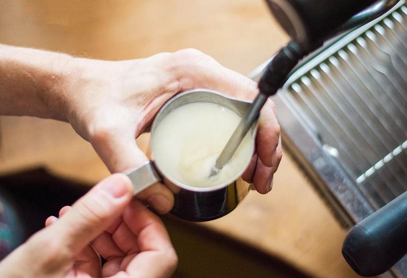 Giữ đầu đũa hơi cạnh bình, tạo thành một vòng xoáy trong sữa