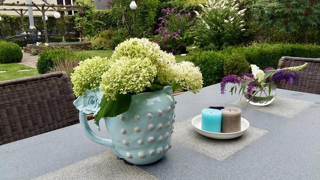 Kan met hortensia's op tuintafel