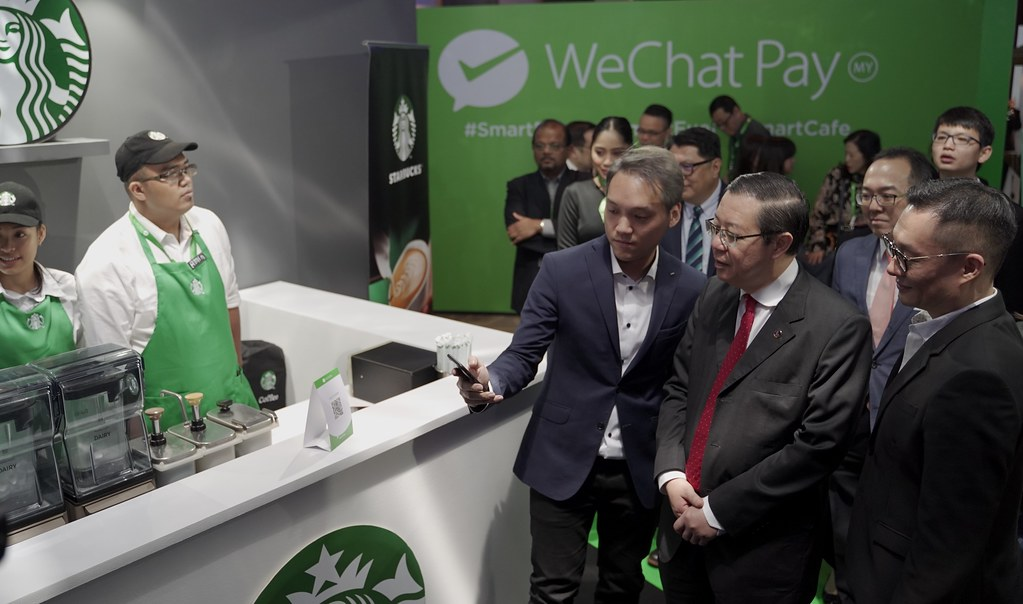 (From left) Jason Siew, CEO of WeChat Pay MY, presenting demonstrating how to make orders and payments via WeChat Pay MY to YB Tuan Lim Guan Eng, Finance Minister of Malaysia, while Poshu Yeung, Vice President, International Business Group at Tencent looked on.