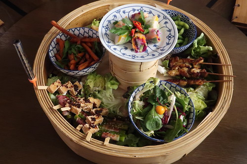Coa Plate mit dreierlei Saté, verschiedene Sommer- und Frühlingsrollen, Edamame, dreierlei Dumplings und Süßkartoffelpommes (wie serviert)