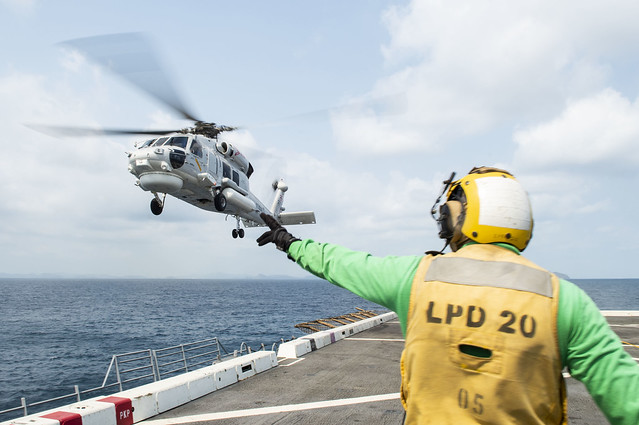 GULF OF THAILAND (Feb. 14, 2019) – Aviation Structural Mechanic 3rd Class Andrew Jerauld, from North Attleboro, Mass., signals an S-70B Seahawk helicopter, assigned to the Royal Thai Navy landing platform dock ship HTMS Angthong (LPD 791), as it takes off from the flight deck of the amphibious transport dock ship USS Green Bay (LPD 20) during cross deck flight operations. Green Bay, part of the Wasp Amphibious Ready Group, with embarked 31st Marine Expeditionary Unit (MEU), is in Thailand to participate in Exercise Cobra Gold 2019. Cobra Gold is a multinational exercise co-sponsored by Thailand and the United States that is designed to advance regional security and effective response to crisis contingencies through a robust multinational force to address common goals and security commitments in the Indo-Pacific region. (U.S. Navy photo by Mass Communication Specialist 2nd Class Anaid Banuelos Rodriguez)