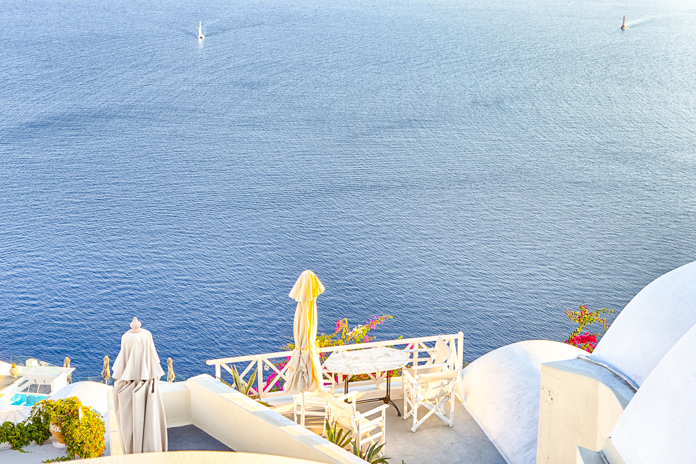 European Scenic Destinations. Pale Houses And Open Air Restaurant of Oia Village in Santorini in Greece with Sailing Boats on Background.