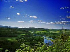 The DE River is lined by luscious green mountains and a bright blue sky