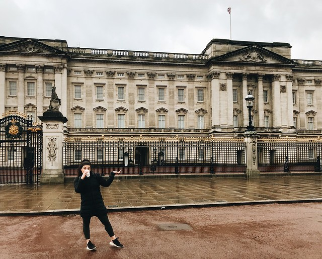 A girl standing in front of Buckingham palace.